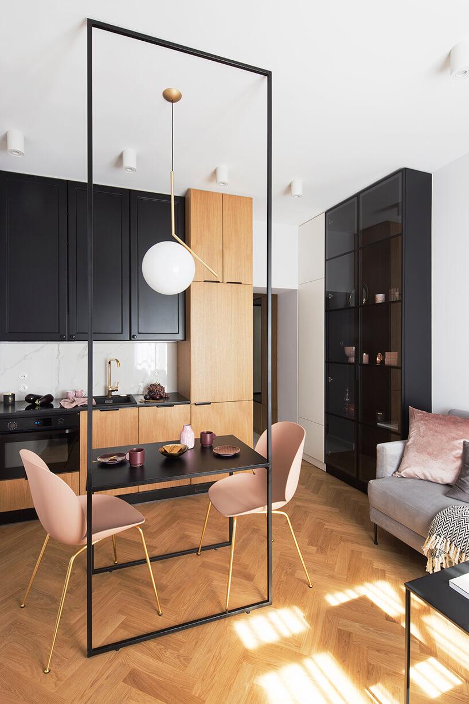 kawalerka od ZAZA Studio czarno brązowy aneksy kuchenny jako tło dla czarnego stolika zdwoma różowymi krzesłami ze złotymi nogami