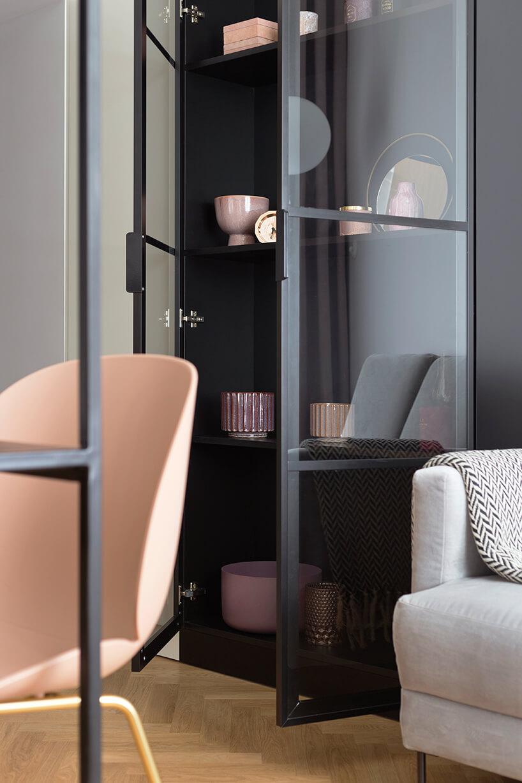 kawalerka od ZAZA Studio czarna wysoka szafka zprzeszklonymi drzwiami obok szarej sofy