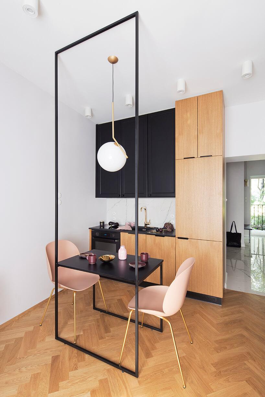 kawalerka od ZAZA Studio czarno brązowy aneksy kuchenny jako tło dla czarnego stolika zdwoma różowymi krzesłami ze złotymi nogami na ładnym parkiecie