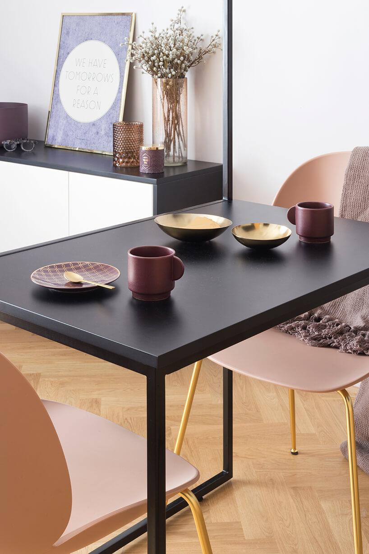 kawalerka od ZAZA Studio czarny mały stolik zbordowymi kubkami italerzykami zdwoma krzesłami na złotych nogach
