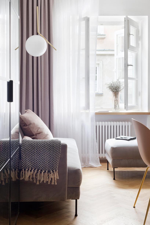 kawalerka od ZAZA Studio małą sofa pod lampą wiszącą na złotym elemencie na tle różowej zasłony p