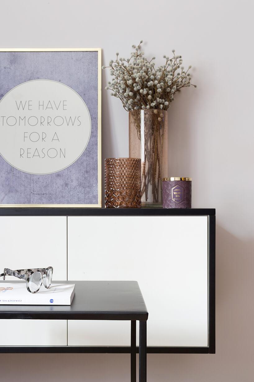 kawalerka od ZAZA Studio czarny stolik na tle biało czarnej podwieszonej szafki ze stojącym fioletowym plakatem wzłotej ramie