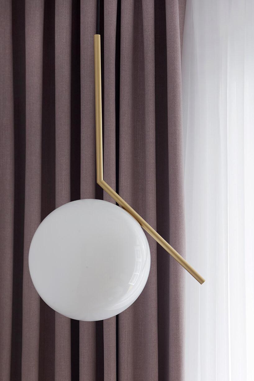 kawalerka od ZAZA Studio elegancka lampa wisząca biały klosze na złotym uchwycie na tle fioletowej zasłonki