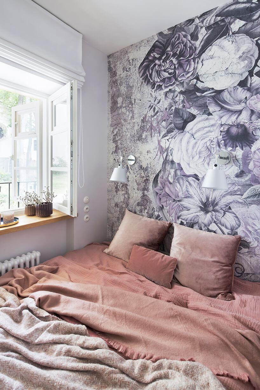 kawalerka od ZAZA Studio duże łóżko pod same ściany na tle ściany ztapetą wfioletowe kwiaty
