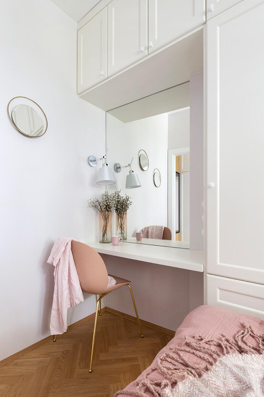 kawalerka od ZAZA Studio biała toaletka zdużym lustrem iróżowym krzesłem na złotych nogach wotoczeniu białej zabudowy