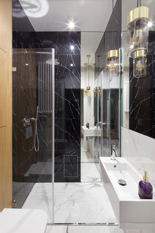 kawalerka od ZAZA Studio kamienna czarno białą łazienka zdużym lustrem iprzeszklony natrysk