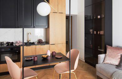 kawalerka od ZAZA Studio czarno brązowy aneksy kuchenny jako tło dla czarnego stolika z dwoma różowymi krzesłami ze złotymi nogami