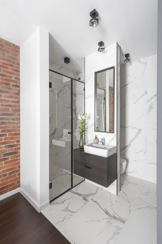 kawalerka wstylu industrialnym od decoroom prysznic iumywalka na tle kamiennego białego aneksu łazienkowego