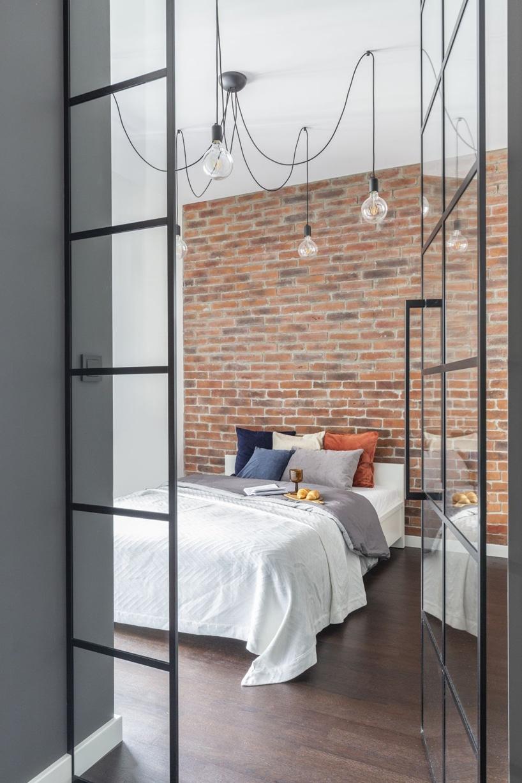 kawalerka wstylu industrialnym od decoroom widok na sypialnię iduże łózko na tle ceglanej ściany