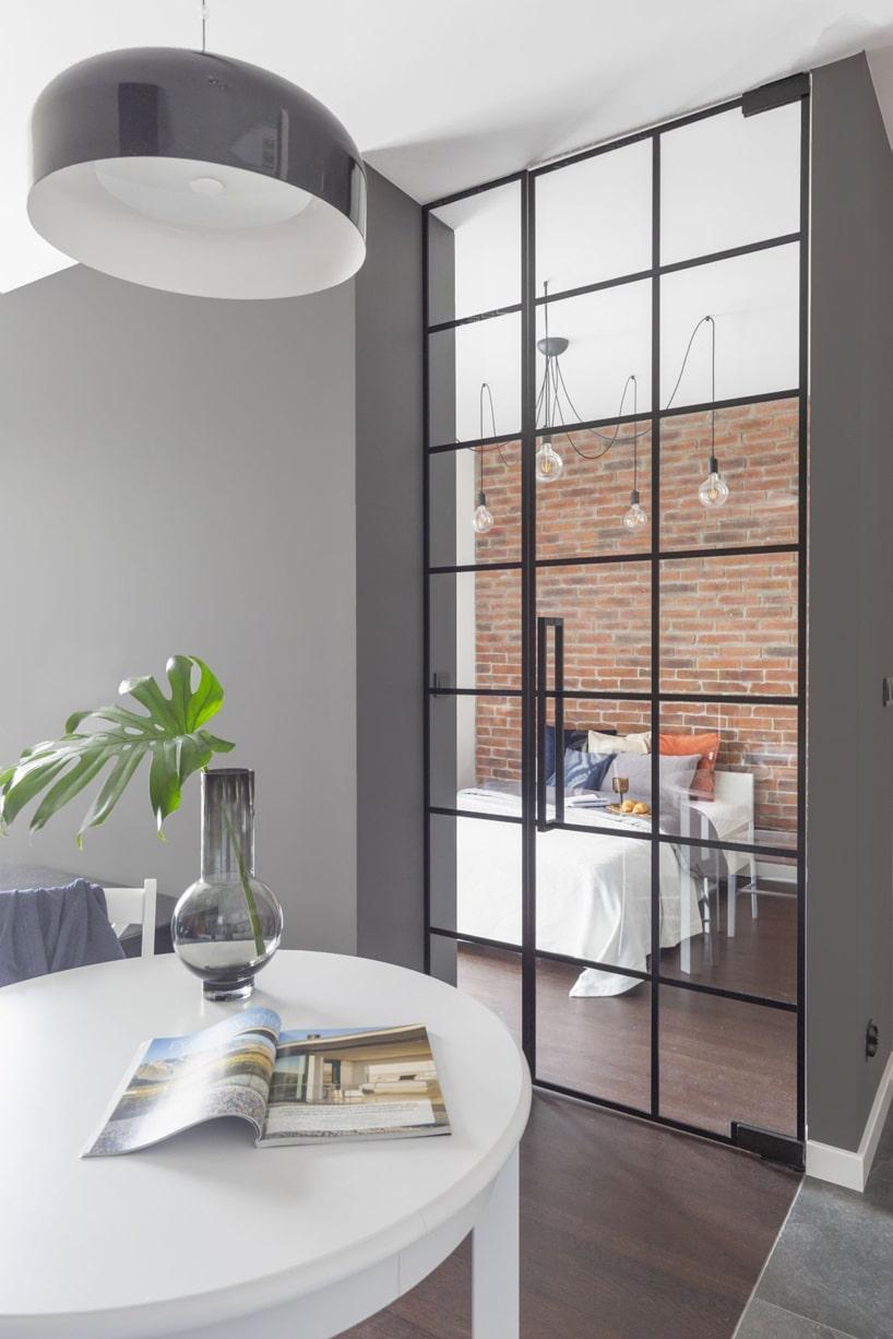 kawalerka wstylu industrialnym od decoroom biały stolik na tle szklanych drzwi wczarnej ramce do sypialni