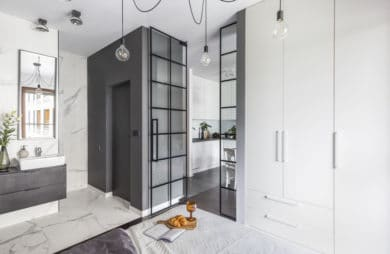 kawalerka w stylu industrialnym od decoroom biały aneks kuchenny z szarym blatem biała zabudowa obok szklanych drzwi z czarnymi ramkami