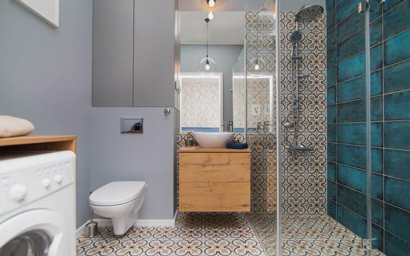 łazienka zdrewnianą szafką, wzorzystymi iciemno zielonymi kafelkam
