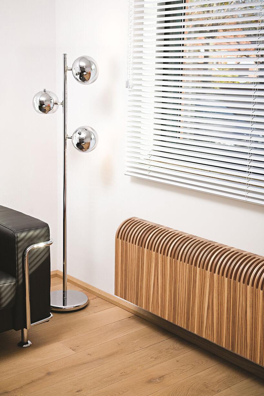 drewniany grzejnik obok chromowanej lampy stojącej