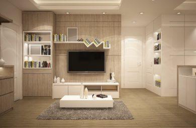 beżowe ciepłe wnętrze salonu z białą kanapą i podnóżkiem utrzymane w jasnych barwach