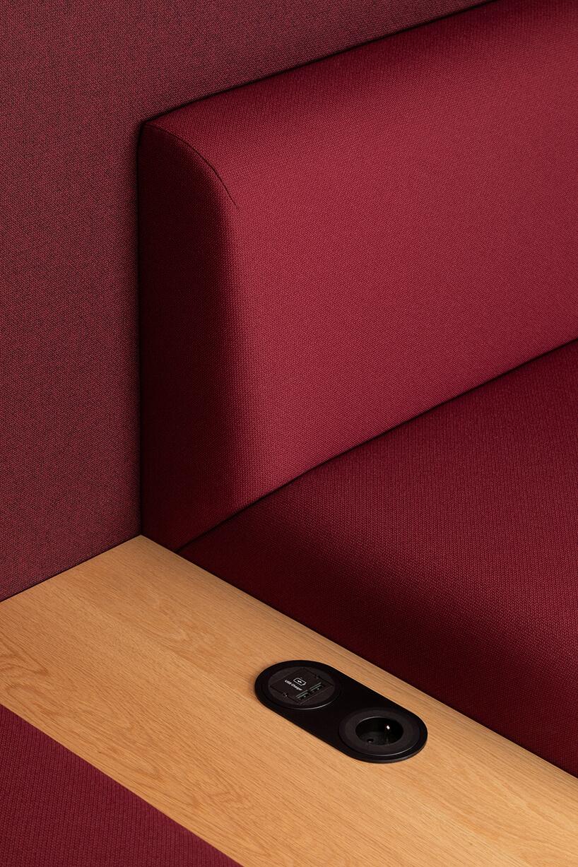 bordowa sofa zdrewnianą wstawką zczarnym gniazdkami
