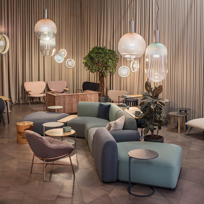 aranżacja wnętrza znowoczesnymi siedziskami wpastelowych kolorach pod fantazyjnymi lampami wiszącymi