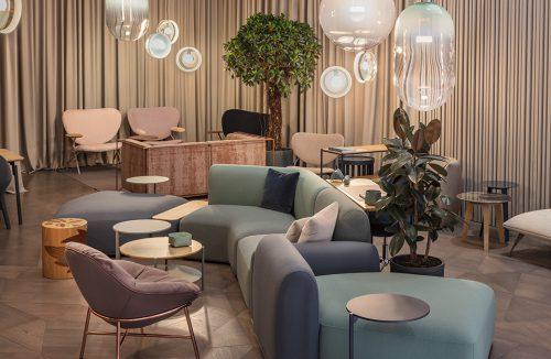 aranżacja wnętrza z nowoczesnymi siedziskami w pastelowych kolorach pod fantazyjnymi lampami wiszącymi