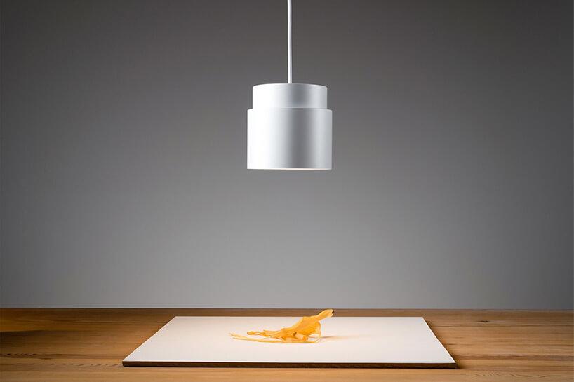 biała wisząca nad stołem lampa-reflektor