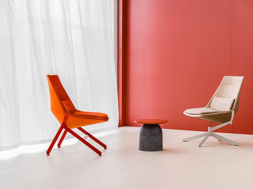 dwa fotele zserii Frank od MDD przy małym stoliku zczerwonym blatem ikamienną podstawą