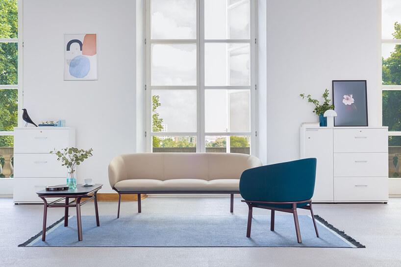 szara sofa iniebieski fotel zserii Grace waranżacji poczekalni zdużym oknem