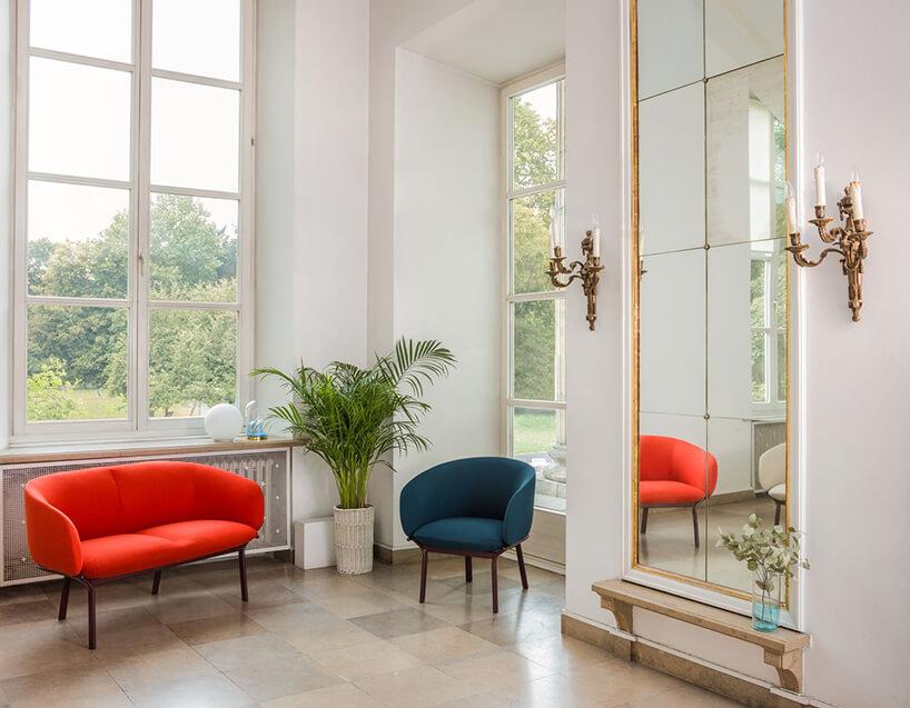 czerwona sofa iniebieski fotel zserii Grace od MDD obok wysokiego lustra na tle wysokich okien