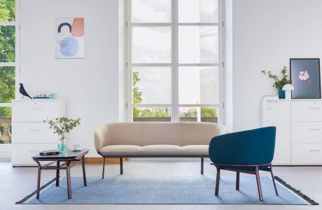 szara sofa i niebieski fotel z serii Grace w aranżacji poczekalni z dużym oknem