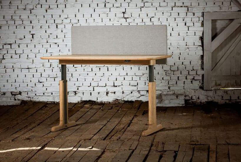 ruchome biurko zjasnym drewnem oraz szarymi pleckami na tle ceglastej ścianie