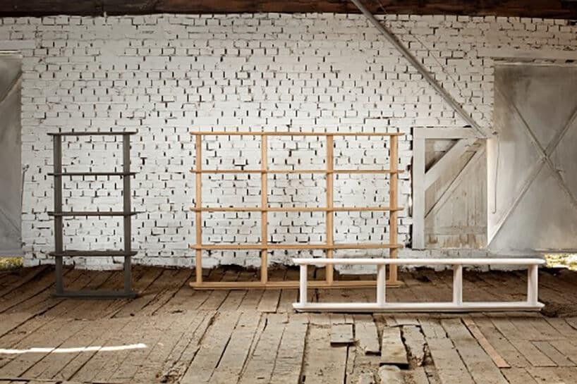klika drewnianych regałów wróżnych jasnościach drewna wdużym pomieszczeniu zceglaną ścianą