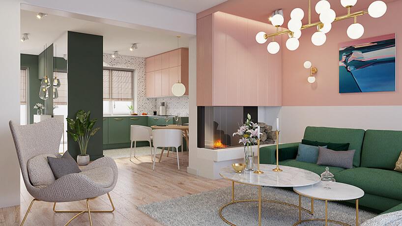 nowoczesny salon zjasną drewnianą podłogą zzieloną sofą iszarym fotelem na tle kominka