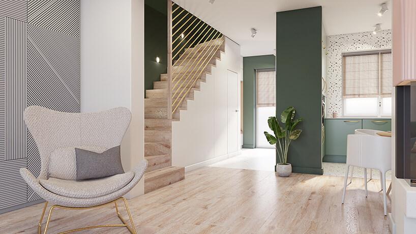 szary fotel na złotym cienkim stelażu wsalonie na tle drewnianych schodów