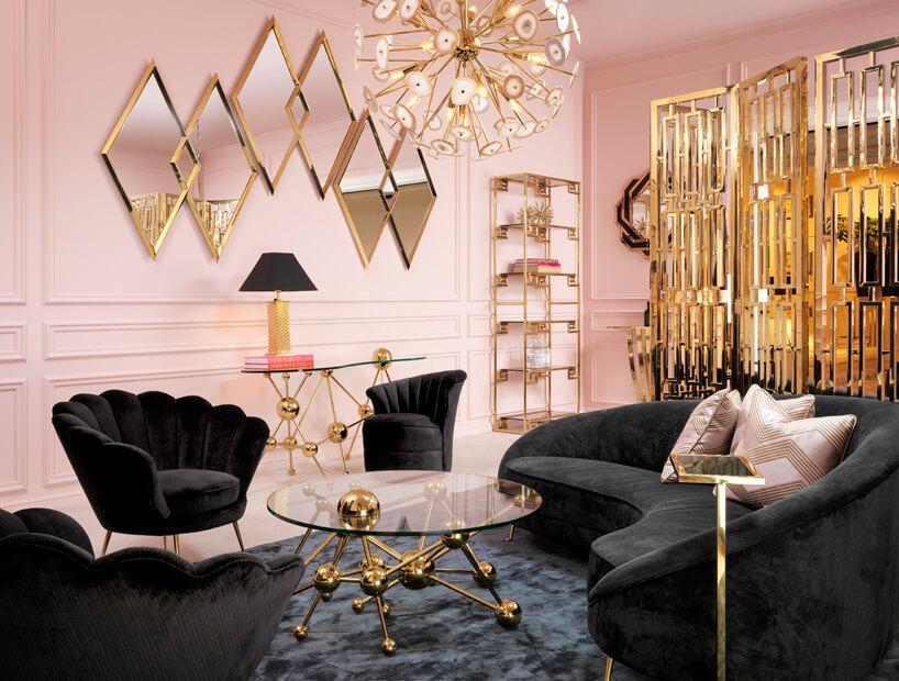 różowe wnętrze ze złotymi akcentami iczarną sofą