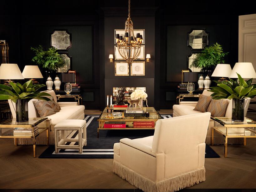 wnętrze salonu zczarnymi ścianami ibiałymi meblami do siedzenia
