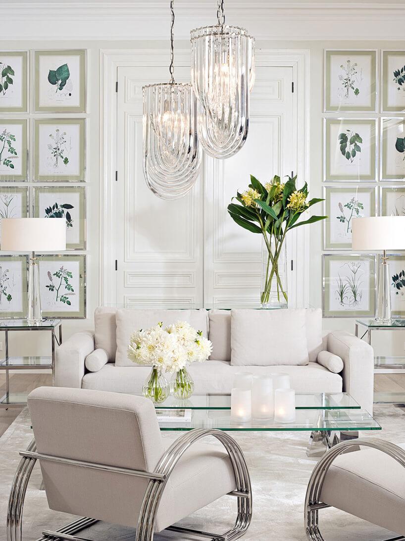 biała sofa idwa fotele za szklanym stolikiem na tle białej ściany zobrazami