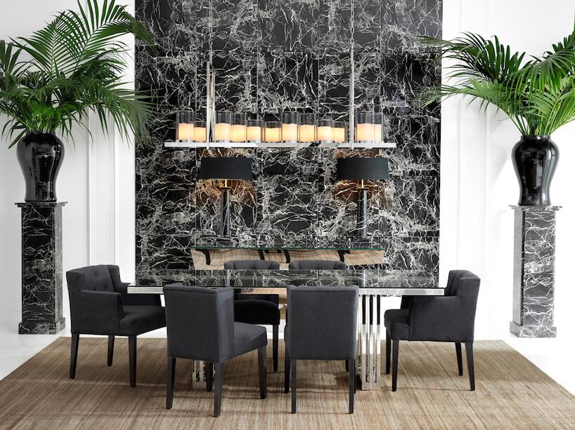 jasne wnętrze jadalni zkamieniem na jednej ze ścian jako tło stołu zczarnymi krzesłami