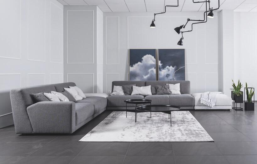 dwu częściowy zestaw sof za ciemnym stolikiem na białym dywanie