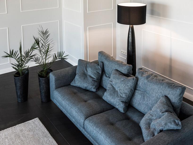 ciemno niebieska sofa na tle ciemnej podłogi