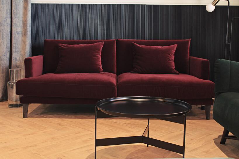 bordowa sofa na drewnianej podłodze wciemnym wnętrzu