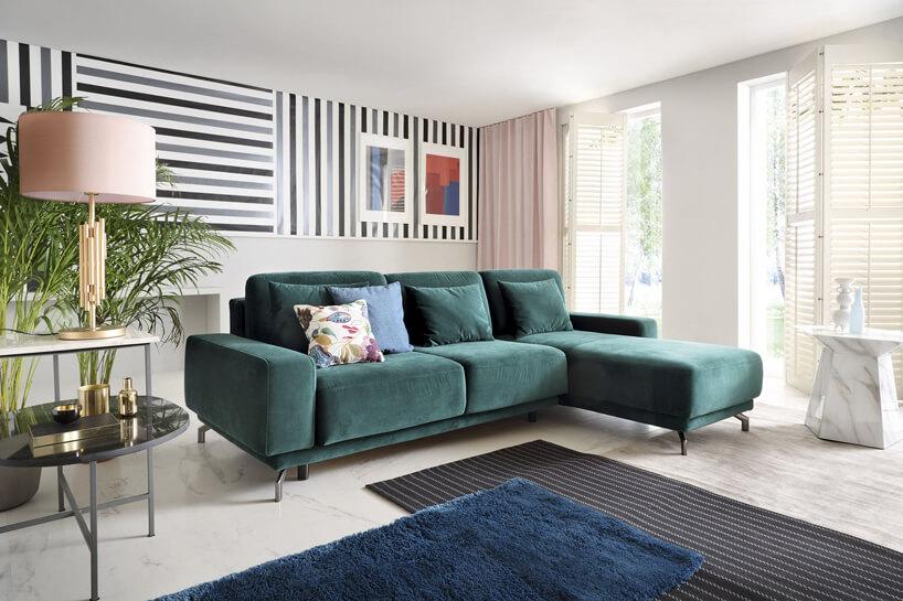 ciemno zielona sofa waranżacji salonu na jasnej podłodze