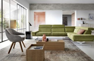 zielona sofa w przestronnym salonie z wysokimi oknami
