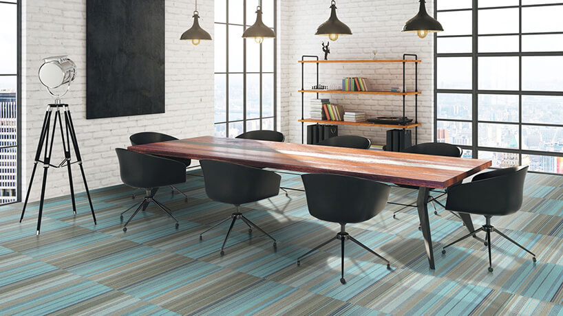 elegancka sala konferencyjna zdużym czarnym stołem zdrewnianym blatem na podłodze wszare iniebieskie paski