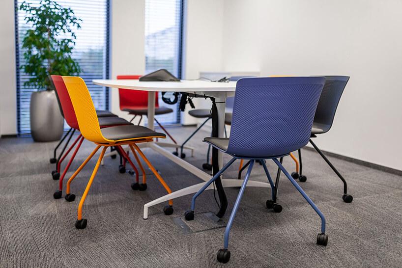 mała sala konferencyjna wbiałym biurze zbiałym stołem oraz korowymi krzesłami na kółkach