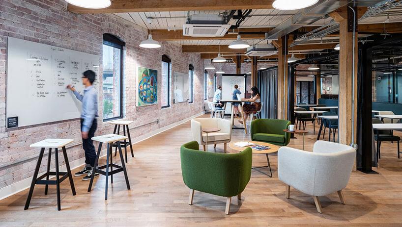 open space zceglanymi ścianami idrewnianymi filarami zdrewnianą podłogą ibiałymi izielonymi fotelami