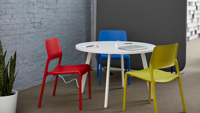 nieduży biały okrągły stolik ztrzema kolorowymi krzesłami na tle szarej ściany