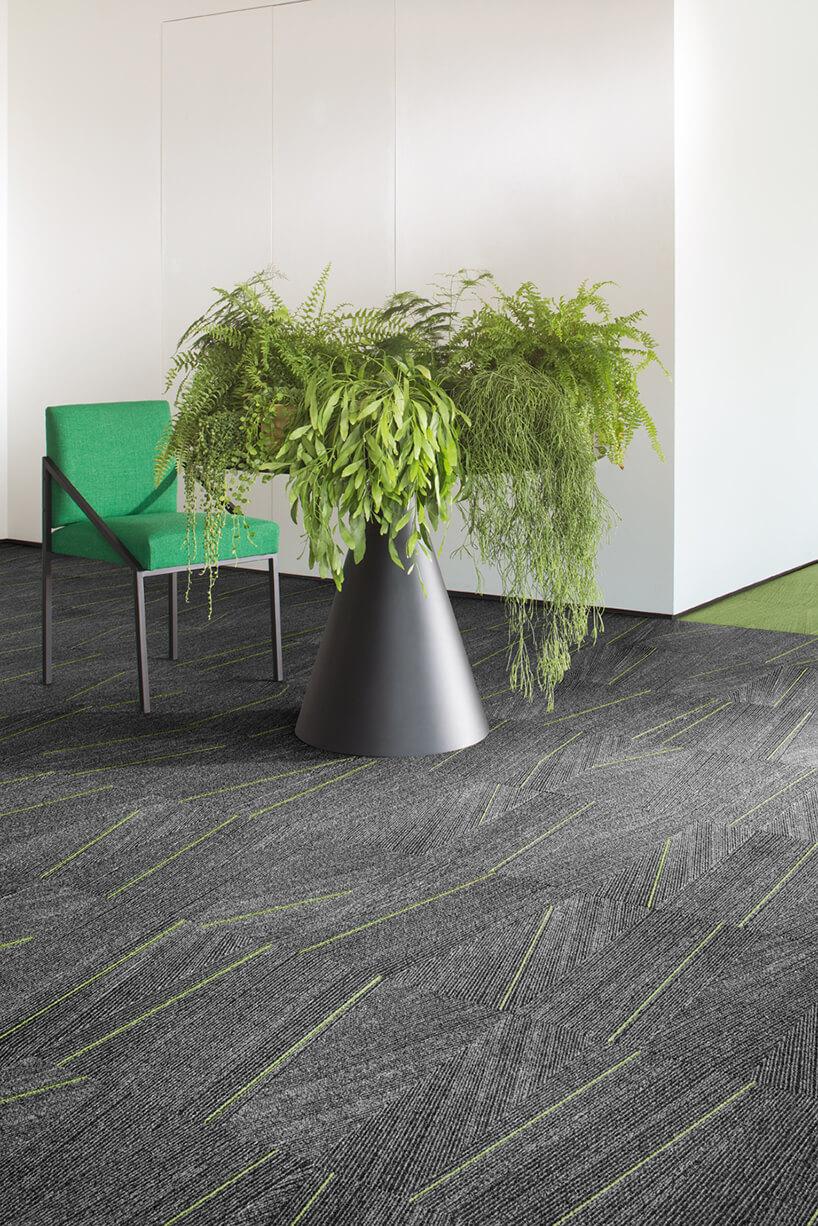 zielony fotel obok kwietnika zroślinami na szarej wykładzinie zzielonymi paskami