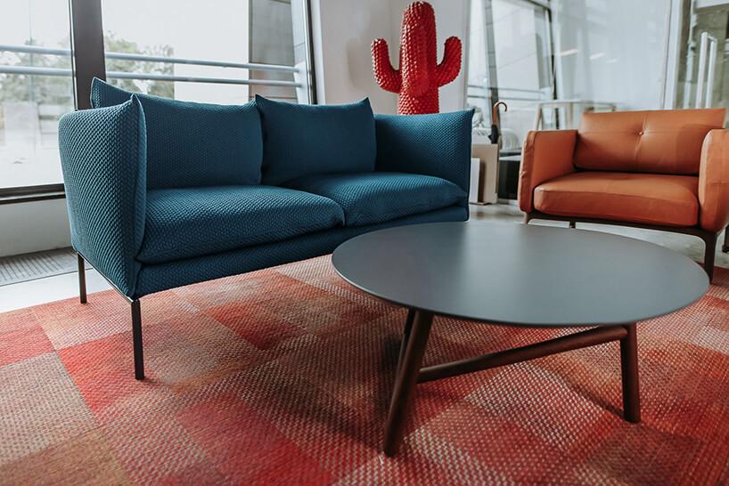 małą niebieska sofa na wysokich nogach obok pomarańczowego fotela przy okrągłym stoliku na czerwonym dywanie