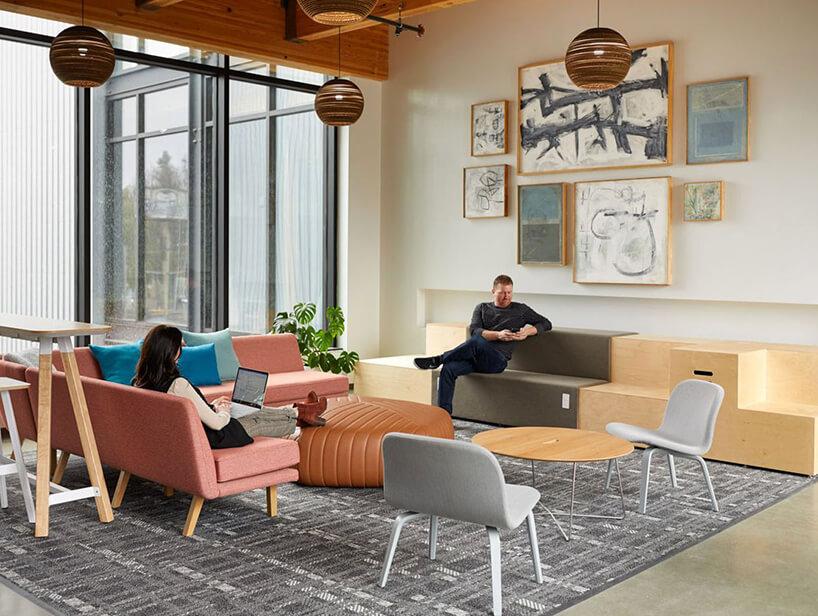 nowoczesna przestrzeń do relaksu zkolorowymi siedziskami na szarym dywanie na tle obrazów