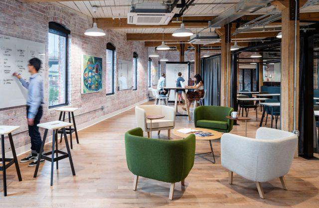 open space z ceglanymi ścianami i drewnianymi filarami z drewnianą podłogą i białymi i zielonymi fotelami