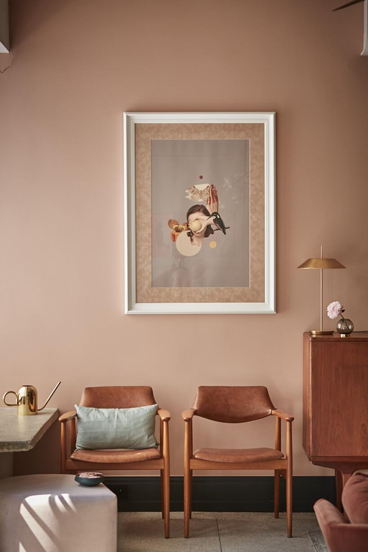 brązowe wnętrze zobrazem wbiałej ramie na dwoma brązowymi drewnianymi krzesłami ze skórzanym oparciem isiedziskiem