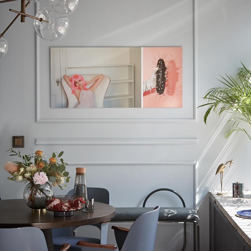 jasne wnętrze salonu zbiałą ścianą zplakatem zciemno brązowym okrągłym stole