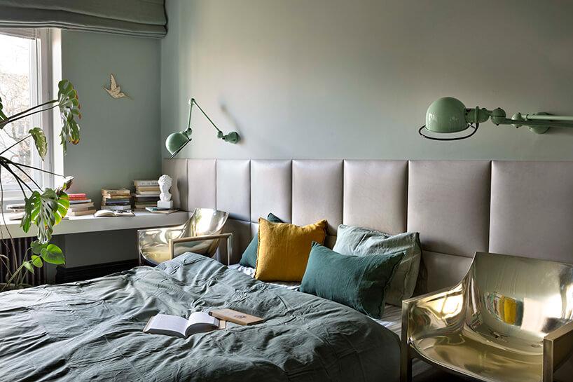 duża sypialnia zzieloną ścianą iczęściowo obitą skórzanymi poduszkami jako tło dla dwóch błyszczących krzeseł